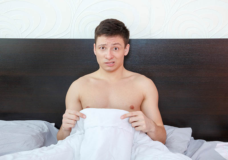 a man in bed worrying about his penis