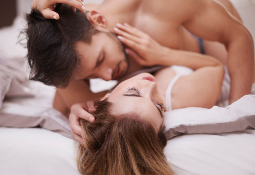 a man and woman having sex in bed