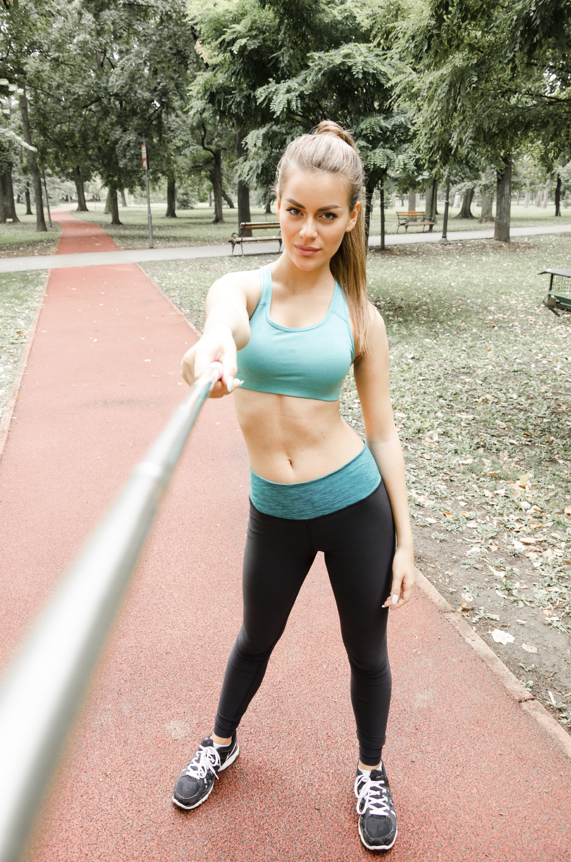 fitness girl taking a selfie with a selfie stick