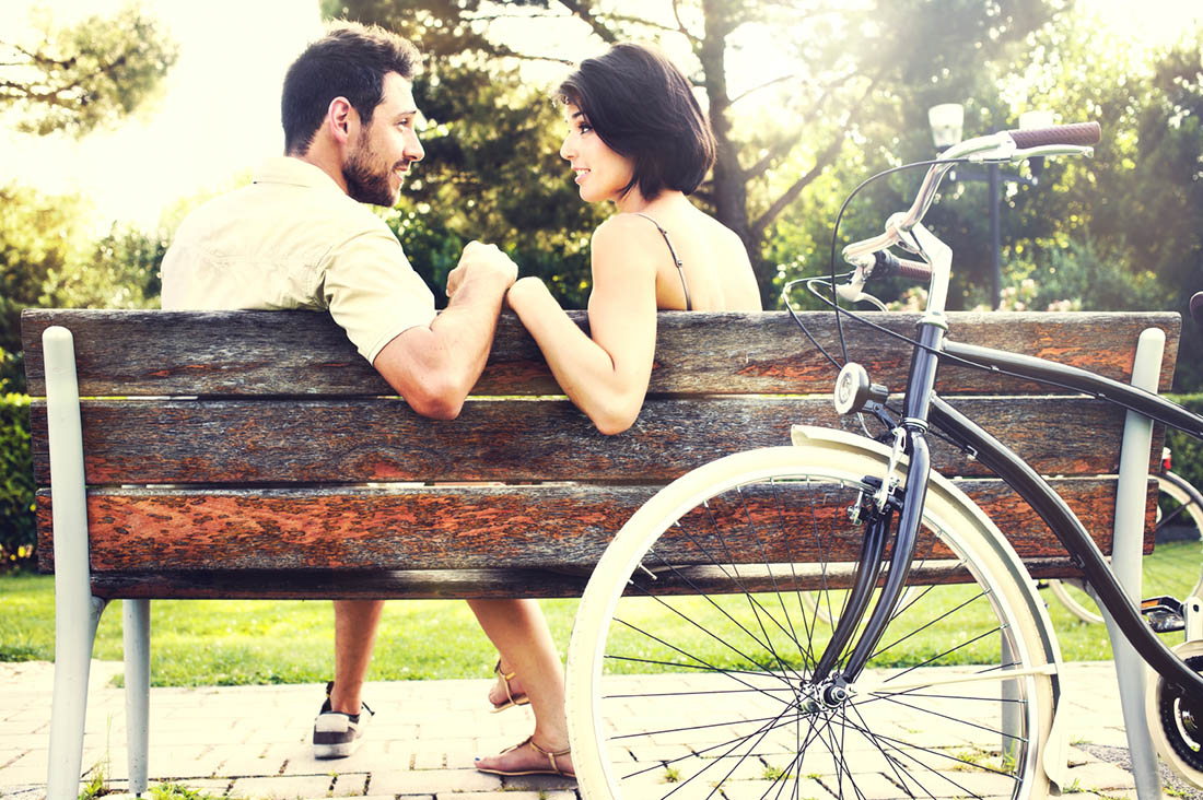 a man and woman chatting on a park bench