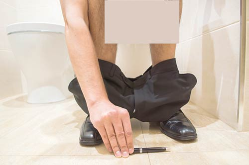 A man in a bathroom stall managing his penis extender in private.