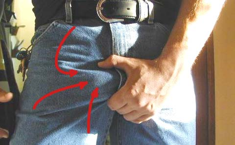A man grabbing his crotch because he wore his penis extender too long that day.