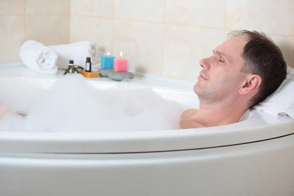 A man in a bathtub using a penis pump.
